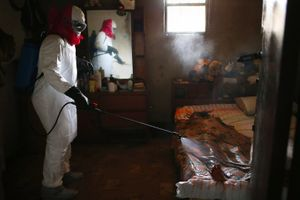 """Bedroom. A burial team sprays disinfectant over the body of a woman suspected of dying of Ebola in her home. From the series """"Ebola Crisis Overwhelms Liberian Capital."""" Winner of L'Iris d'Or, 2015 Sony World Photography Awards."""