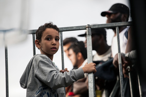 Young syrian refugee is playing in the front of the barriers, which prevent refugees from the Middle East to enter the Schengen zone, Rigonce, Slovenia.