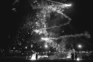 A Buddhist monk snaps the falling fireworks with his phone camera