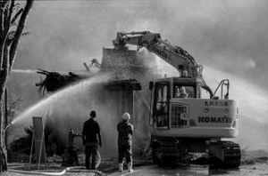 10 - Purtroppo i pompieri prendono atto che l'unica soluzione è abbattere il tetto in fiamme con una escavatrice parcheggiata nelle vicinanze. Non è stato possibile salvare questa storica casa di paglia.