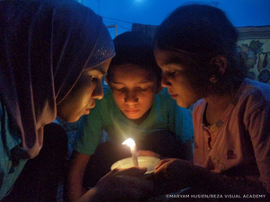 Nights in the camp are lit only by the light of a candle or lantern. Young photographer Maryam Husein created this image of her brother and her two sisters—a glimpse of their intimacy...