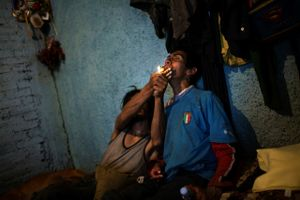 © David Rochkind, One man helps another smoke crack in Mexico City, from the series Heavy Hand, Sunken Spirit.  Honorable Mention, LensCulture International Exposure Awards 2010