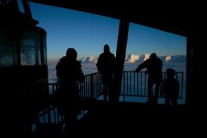 Skieurs en contre jour à la station de télécabine au sommet du Moléson, Gruyère.