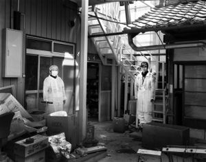 """Takami and Noriko Ohara came to check their abandoned house in the exclusion zone. They used to run a small local shop. Their old home is damaged as it has been empty for over two years. They would like to come back to live but they are not optimistic. Tomioka town, Fukushima prefecture. From the series """"Fragments/Fukushima"""" © Kosuke Okahara"""