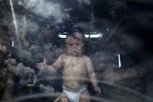 Refugee family and their child in the bus at the Izvarino border crossing point