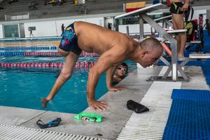 Moises Fuentes Garcia, 41, does pushovers on the border of a pool after a training session at the Simon Bolivar Aquatic Complex, Bogotá, June 2016.