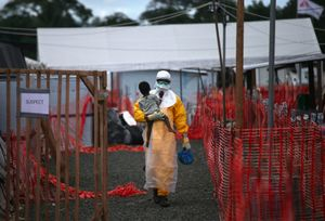 """Suspect. An MSF health worker in protective clothing carries a sick girl at an Ebola treatment center. From the series """"Ebola Crisis Overwhelms Liberian Capital."""" Winner of L'Iris d'Or, 2015 Sony World Photography Awards."""