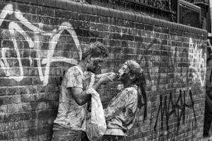 A paint-covered couple share a drink.