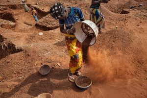 Women dig on the surface where they are repeatedly separating the heavier particles from dust, after which, they will pan it for gold. © Matjaz Krivic