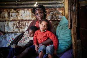 Maureen and her two children pose for a portrait at a friend's shack. They used to live in a 3 square meter sized shack in the township of Katutura. A storm destroyed it, so now Maureen and her children have to sleep out in the open. Sometimes they find shelter at other people's shacks. In winter the temperatures in Namibia can sink as low as minus 10 degrees celsius during the night.