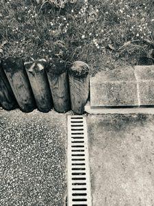 Asphalt, wooden Posts, Grass and Gutter
