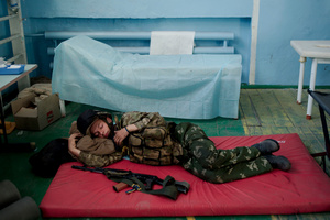 "Volunteer from battalion ""Donbass"" sleeps in between duty at the checkpoint. On the background – a ""bandaging table"". August 27, 2014."