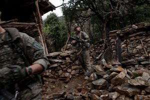 A squad of U.S. soldiers from Bravo Company of the 1st Infantry Division enter Loi Kolay, a known insurgent village, in the Korengal Valley, Afghanistan, on April 7, 2009. After leaving the village the patrol was ambushed by insurgents. © Adam Ferguson