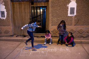 Girls playing hopscotch in the street, Calca, Peru