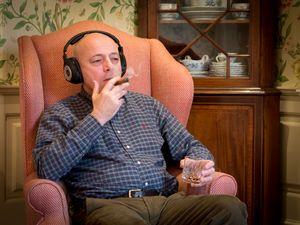 Simon smokes a cigar while listening on headphones