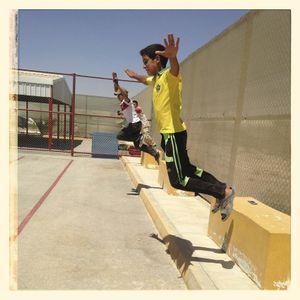 Children jump off concrete blocks in the sports pitch at Za'atari refugee camp