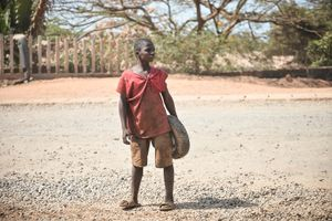 A boy waits to cross a road in Freetown. He carries a small wheel and tired in his hands.