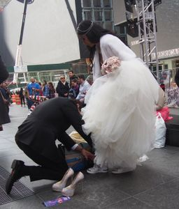 GROOM HELPS STILL-VEILED BRIDE