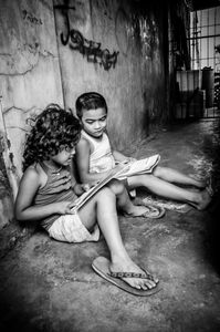 It started drizzling. The children sat down in the narrow corridor, opened their books and began reading out loud.