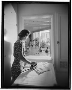 """Woman looking into backyard from utility room, James W. Clyne residence, Malibu, CA c. 1946. From the photobook """"Modern Photography and the American Dream"""" © Maynard Parker"""