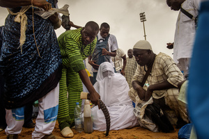 A marabout in a wight Burka, hired by wrestler Yekini, puts a spell on the sands of the arena of the the stadium Demba Diop on July 24 2016, before the fight between Yekini and Lac de Guiers 2. Many wrestling fans who watched this mysterious person in white on TV said that they had never witnessed such a thing before.