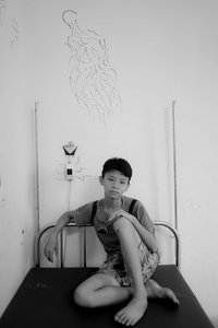 Portrait of Mạnh in his bedroom with his drawing of a ghost on the wall