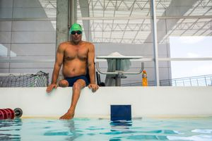 Moises Fuentes Garcia, 41, sits on the border of the swimming pool, before the beginning of his training session at the Simon Bolivar Aquatic Complex, Bogotá, June 2016.
