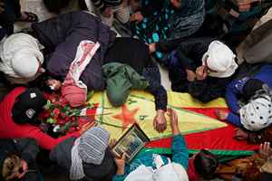 During a ceremony in Kobane, Syria, on 2 April, 2015, mourners gather by the coffin of their loved ones who were killed during clashes with the Islamic State in one of the frontlines of Kobane, Syria