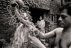 Maya Rani Shingho waiting at the public bath. Shakhari Bazar, 2004. © Munem Wasif