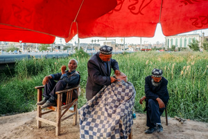 A Uighur shaves a customer at an outdoor stall in old Kashgar, Xinjiang Uighur Autonomous Region, China.