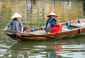 Vietnamese lady crossing the river Bon in Hoi An Old town