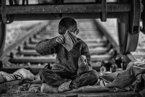 A child under the train tracks is heated by the fire but often the eyes start to burn due to smoking