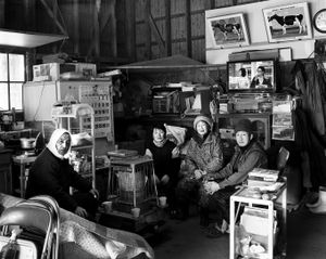 """A portrait of the Sanpei family at their new farm. They were forced to move their cow from the high radiation area which was 26km from the reactor. Still their relocated farm has 1 m sv/h. Their milk doesn't break any laws so they keep producing milk that is mostly used for ice cream. From the series """"Fragments/Fukushima"""" © Kosuke Okahara"""