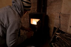 Turning on the wooden stove to get some warm on a cold winter day.