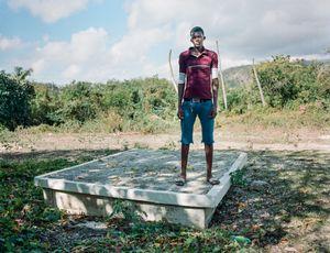 """Donald Lovenson (22) - Corridor, Haiti - Qui repose dans ce tombeau? Ma Maman et ma grand-mère  - Pourquoi aimez vous aller sur cette tombe ? """" J'aime bien me poser là parce que j'ai mes raisons"""" - Qui a dessiné ce monument? Boss Enock"""