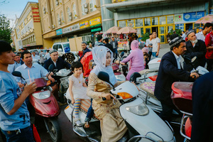 Uighur woman ride on a scooter in a market in old Kashgar, Xinjiang Uighur Autonomous Region, China.