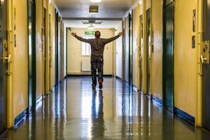 A prisoner walking with his arms out  down one of the corridors of the enhanced wing at HMP/YOI Portland, Dorset.