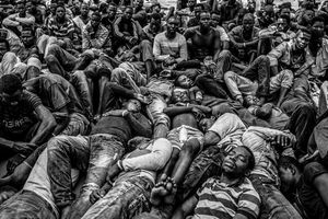 Exhausted Gambian and other West African migrants on the deck of a rescue ship off the coast of Libya