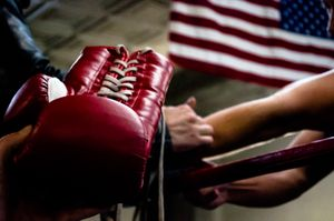 Props master hands actor/director Kent Moran a boxing glove in preparation for a scene.