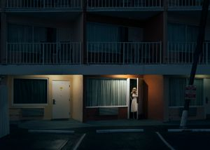 A young blonde woman step out of her motel room. Daytona Shores, Florida.