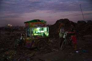 At dusk, a girl recycling worker buys fast-food from a mobile vendor on the edge of Smokey Mountain. © Nigel Dickinson.
