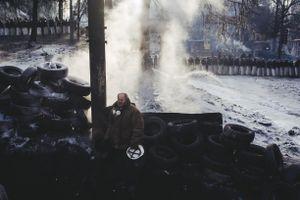 A man stands near barricade on Hryshevskoho street early in the morning. Kyiv, Jan. 27, 2014.