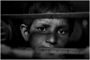 A child gazes through a moving belt.
