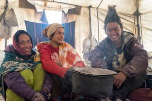 Teenagers warming themselves in a teahouse tent. Upper Dolpo, Nepal, June 2017.