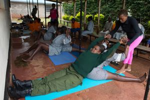Margareth Njeri (23) helps a guard and a prisoner to stretch during a Yoga class in Langata Women Prison.