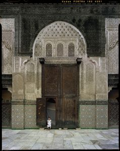 Girl at classroom entrance, Bu Inaniya Madrasa in Fez, Morocco.