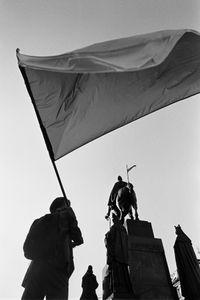 A student waving Czech flag below a statue of St. Wenceslas, patron of Czech lands.