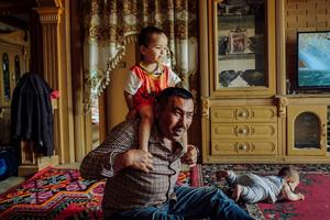 A Uighur man playing with his grandchildren at his apartment house in Kashgar, Xinjiang Uighur Autonomous Region, China.