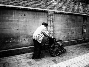 Old man pushing his own wheelchair