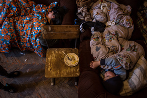 Lusine with her children in their tiny apartment in Gyumri, sleeping all in the only room, that serves also as kitchen and playroom for the family.